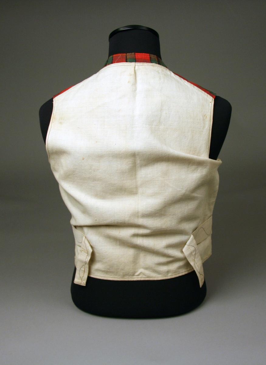 Mansväst av tyg i rött, svart och grönt med bomullsvarp och ylleinslag, dubbelknäppt ingen krage. Foder och rygg av tuskaftat linne.