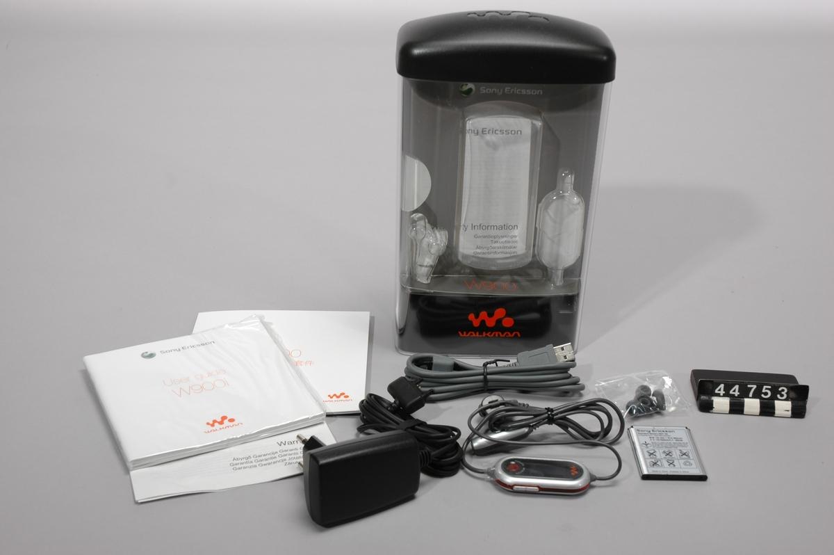 Mobiltelefon, i originalförpackning, obegagnad. Sony ericsson W900i. Förpackningen märkt:W900i Black, DPY 101 2939/26 R1A FI,SV, S/N:BF7ZA72761.  Batteriet märkt: Standard battery BST-33, Type CBA-0001003, S/N:100768SWKFLT, 05W36. MP/FM tillbehör:HPM-80, KRY 1011719 R1A, W0542,Type:CCA-0002009. Laddare: Standard charger CST-60, BML162168/1 R2A,Type: CAA-0002002-BV, S/N: 290B, 05W35, 1100 B. USB kabel.