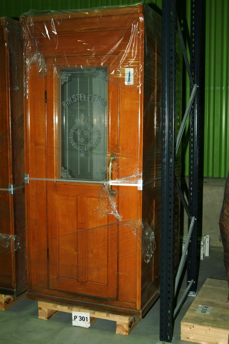 """Talhytt för betjänad telefonstation, hytten märkt """"1"""". Framsida i polerad ek, glas i dörr med riksvapen och texten """"Rikstelefon""""."""