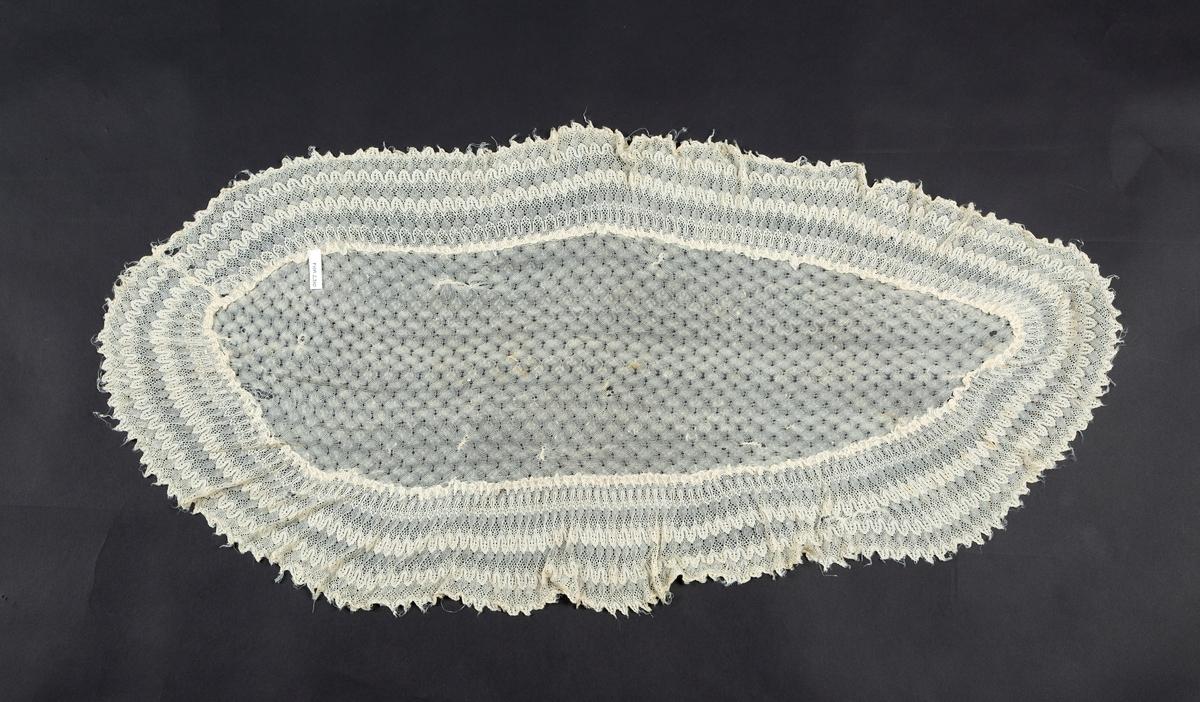 Oval. Kunststrikk med silketråd, antakelig konfeksjon. Lett rynket kant rundt. (se også intern opplysn.