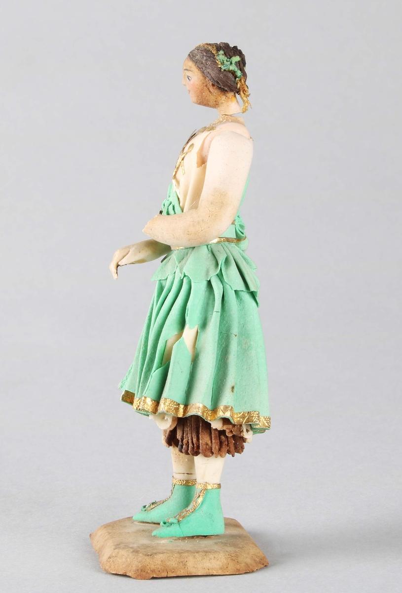 Dragantarbete. Flicka. Flicka i grön kjol, beige och guldfärgat liv, gröna och guldfärgade skor. Brunt hår med bladslingor. Står på rektangulär platta med avfasade hörn.  Fotplattans längd 50x35 mm. Kjolen med skador (bortfall). Höger hand fastlimmad 1983. Vänster hand saknas.  Förvaras i vacker, rektangulär pappask, från 1800-talets andra hälft.  Tillverkad av Hilda Boström (1822-1903), sockerbagare, Borås.  Funktion: Prydnadsfigur