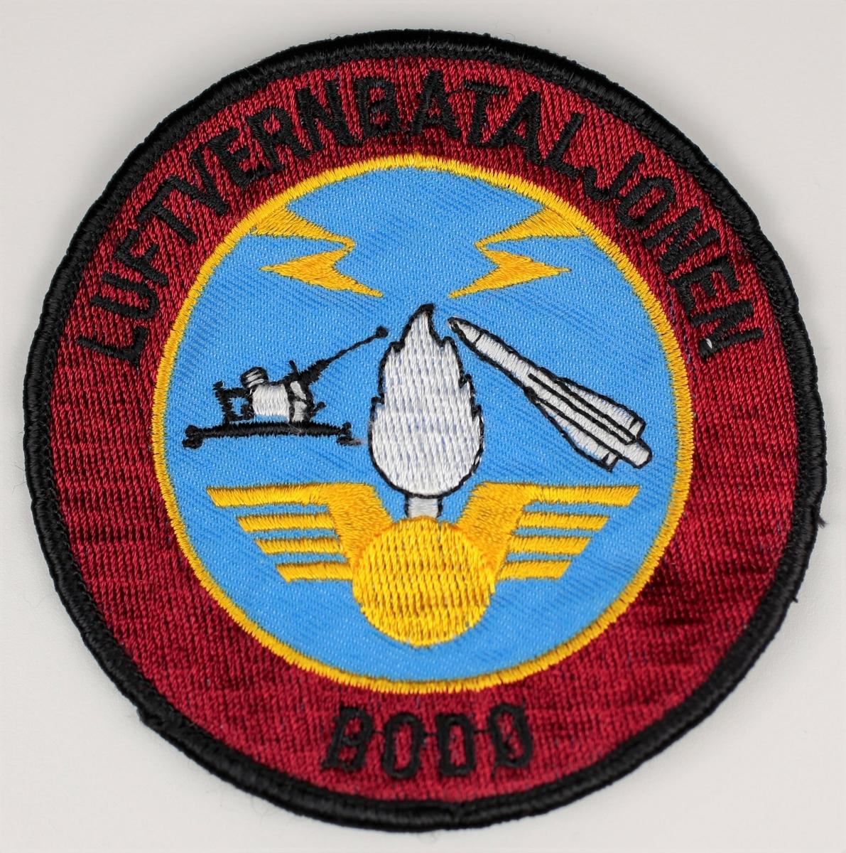 Kanon og missil på blå bakgrunn, rød ramme med tekst: Luftvernbataljonen Bodø