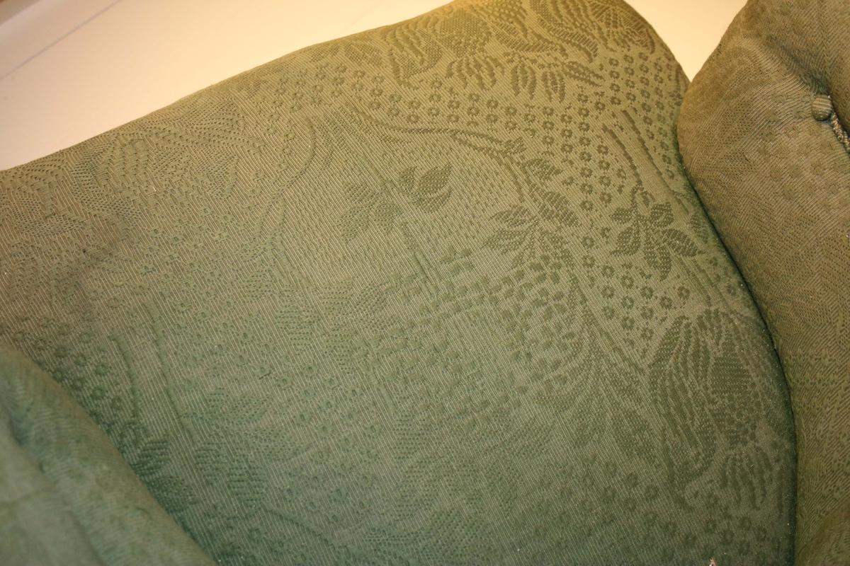 """Fåtölj. Stomme i brunbonat trä. Armstöden framtill, lätt volutformade och räfflade upptill. Benen framtill, raka och svarvade, baktill lätt svängda. Benen med hjultrissor nedtill. I övrigt är fåtöljen, stoppad och helt klädd, i grönt bomullstyg med blad- och blomformationer, omgivna av prickmönster.  Historik: Ada Damm – en av Borås stora historieberättare  Skribenten Ada Damm föddes i Stockholm 1869 men flyttade vid sju års ålder till Borås. Hennes far, August Charles, hade då fått arbete i staden som läkare. Hon var bland de första kvinnorna i Borås som fick utbilda sig vid elementarläroverket, därefter studerade hon språk, konst och musik i Stockholm.  I nästan 50 år skrev Ada Damm i Borås Tidning om livet och människorna i 1800-talets Borås. Materialet hämtade hon från arkiv, brevsamlingar samt genom att intervjua äldre boråsare. Människoöden, händelser, vardag och fest skildras i hennes berättelser. Ofta handlar berättelserna om stadens över- och medelklass. Med sina artiklar och böcker är Ada Damm en av Borås främsta historieskildrare.  Vid sin bortgång 1961 skänktes Ada Damms skrivmaskin och en fåtölj till Borås Museum.   """"Jag vet inte vad jag skulle ta mig till, om jag inte fick skriva. När jag känner behov av avkoppling sätter jag mig vid skrivmaskinen."""""""