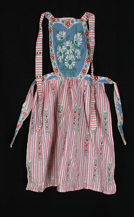 Barnförkläde med bröstlapp. Vitt bomullstyg med lodräta grå och rosa ränder med partier av blommor och blad. Bröstlappen blå och vit med blommor och blad i rött, blått och grönt. Band att knyta runt midja och nacke.
