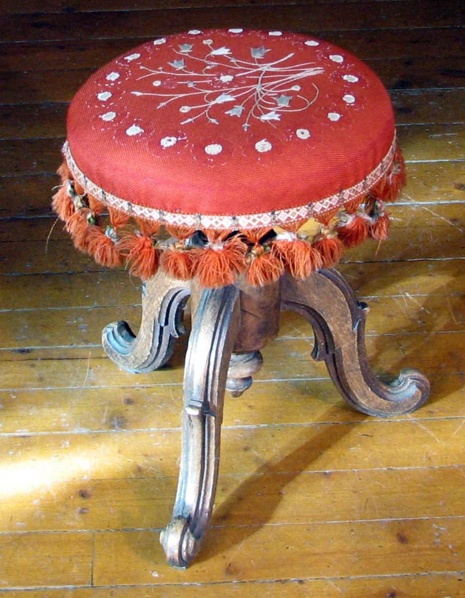 Form: 3 svugne ben, midtstolpe, sete sirkelformet. Hvitt broderi, dusker
