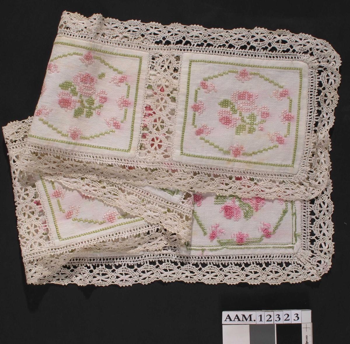 Løper til kommode  eller lign., Stramei, korssting i silkegarn, heklede  blonder. Seks kvadratiske felt brodert med rosa  og lys grønt, mell omverk og kanter avh blonder.  Tilstand: god.