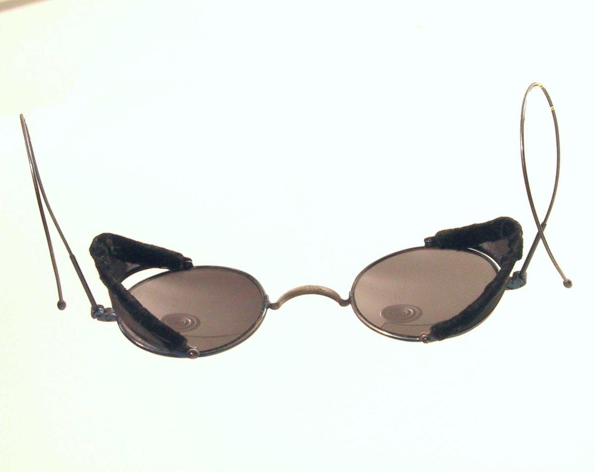 Solbriller, 1 par,  beg. 1900 tallet.   Mørkegrått glass, sort innfatning med  finvegd netting og sort fløyel.    Svakt buede glass, ovale, innerst mot nesen  en skjerm av netting, kantet med fløyel, som kan   Tilstand: god. bøyes ut.