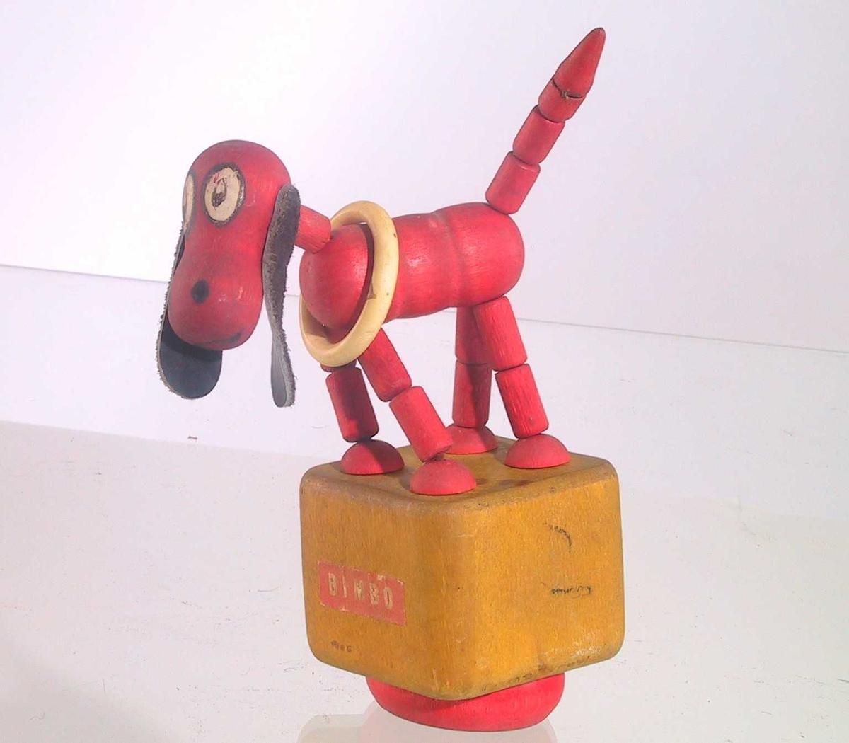 Form: Liten hund med ring rundt halsen og hengende skinn-ører. Leddede bein og hale, står på en trekloss. På undersiden en fjær festet til tråder som holder hunden sammen, slik at dersom man trykker på undersiden beveger hunden på seg.