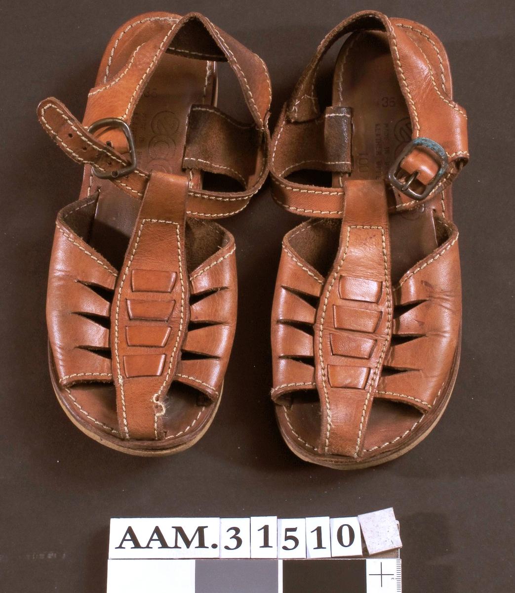 Brune sandaler i lær.  Opprinnelig trolig hvite stikninger langs kantene på lærremmene.  Ankelrem med messingspenne (anløpet).  Flate.  Såle i kunststoff og tre.  Merket med 1007 (modellnummer?)  Størrelse 36