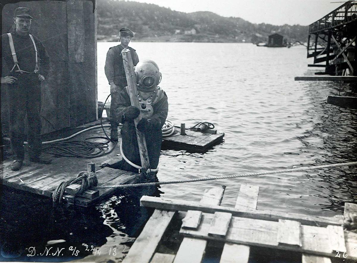 """""""22/04-1913"""" Nitriden. Bygging av kaianlegget. Dykker med hjelpemenn i fullt arbeid. Kaikonstruksjoner til høyre. Tromøysund og Tromøy i bakgrunnen."""