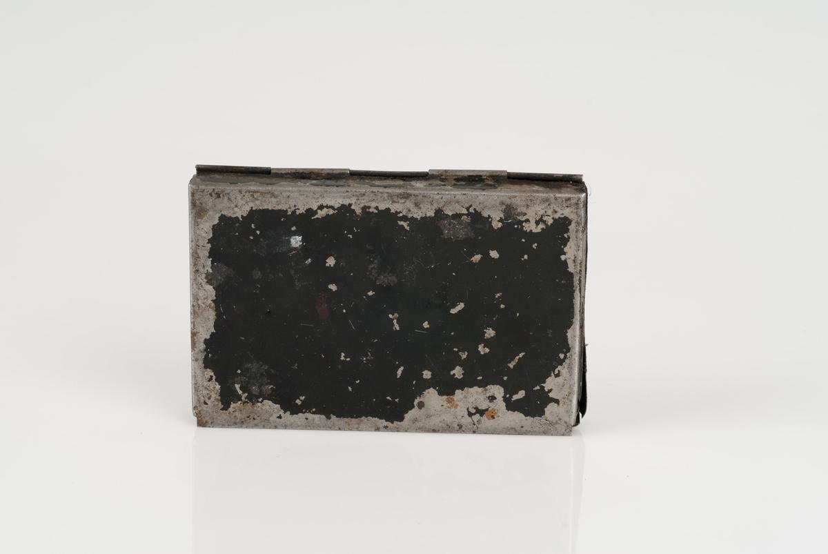 Sort stempelpute i sort stempelbok. Boksen er av metall. En påklistret lapp på lokket med påført tekst som er ikke lesbar.