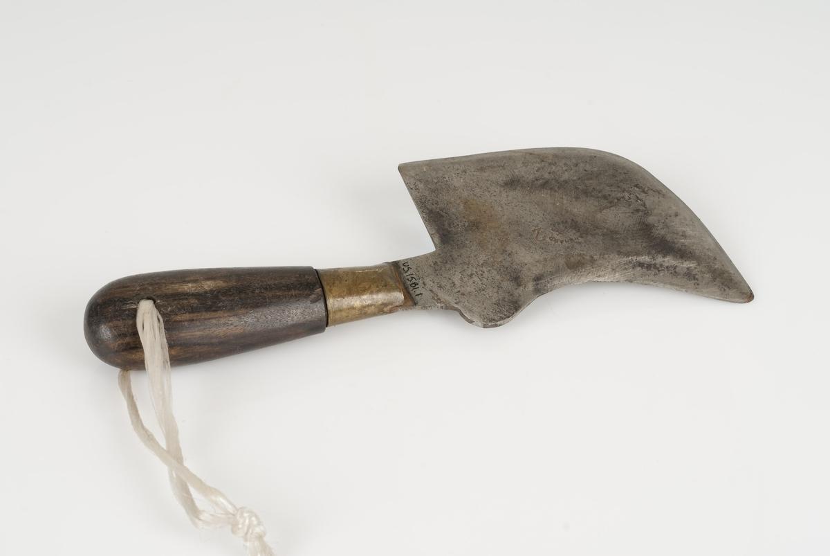 Tapetseringkniv av metall og tre. Knivblad av metall og skaft av tre. Hvit snor festet på enden av skaftet. Ikke lesbar innskrift på knivbladet.