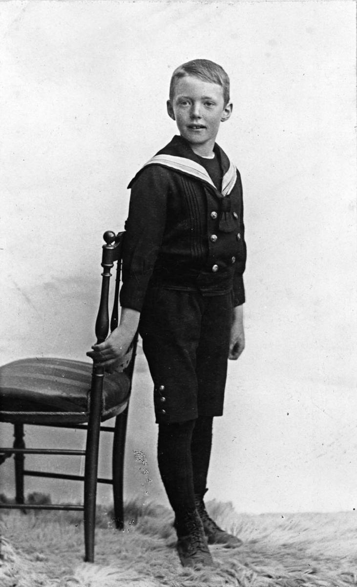 Gutt i matrosdress står ved stol ( atelie-foto)