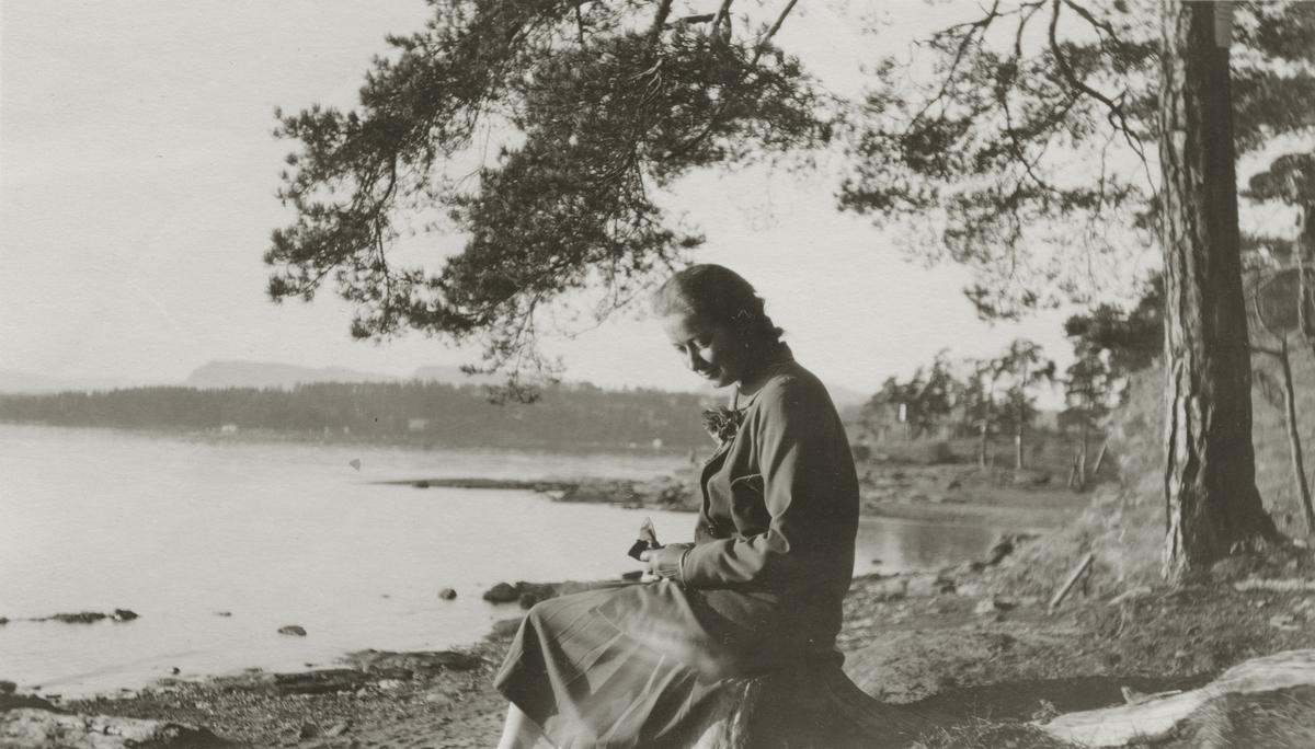 Antatt: Margit Frogner sitter på stubbe ved vannkanten. Skjørt, bleser, veske, hansker og blomst i jakkeslaget.
