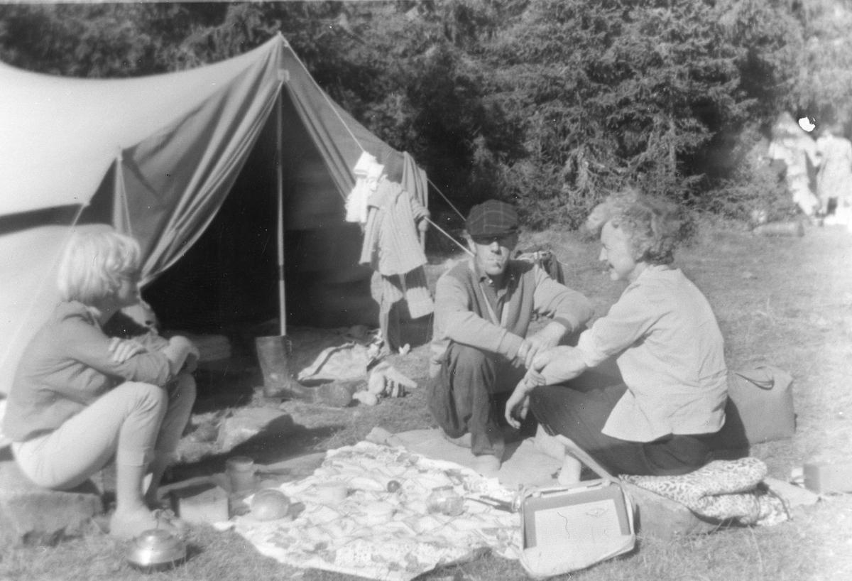 Camping, telttur. Måltid inntas foran teltet med reiseradio som underholdning.