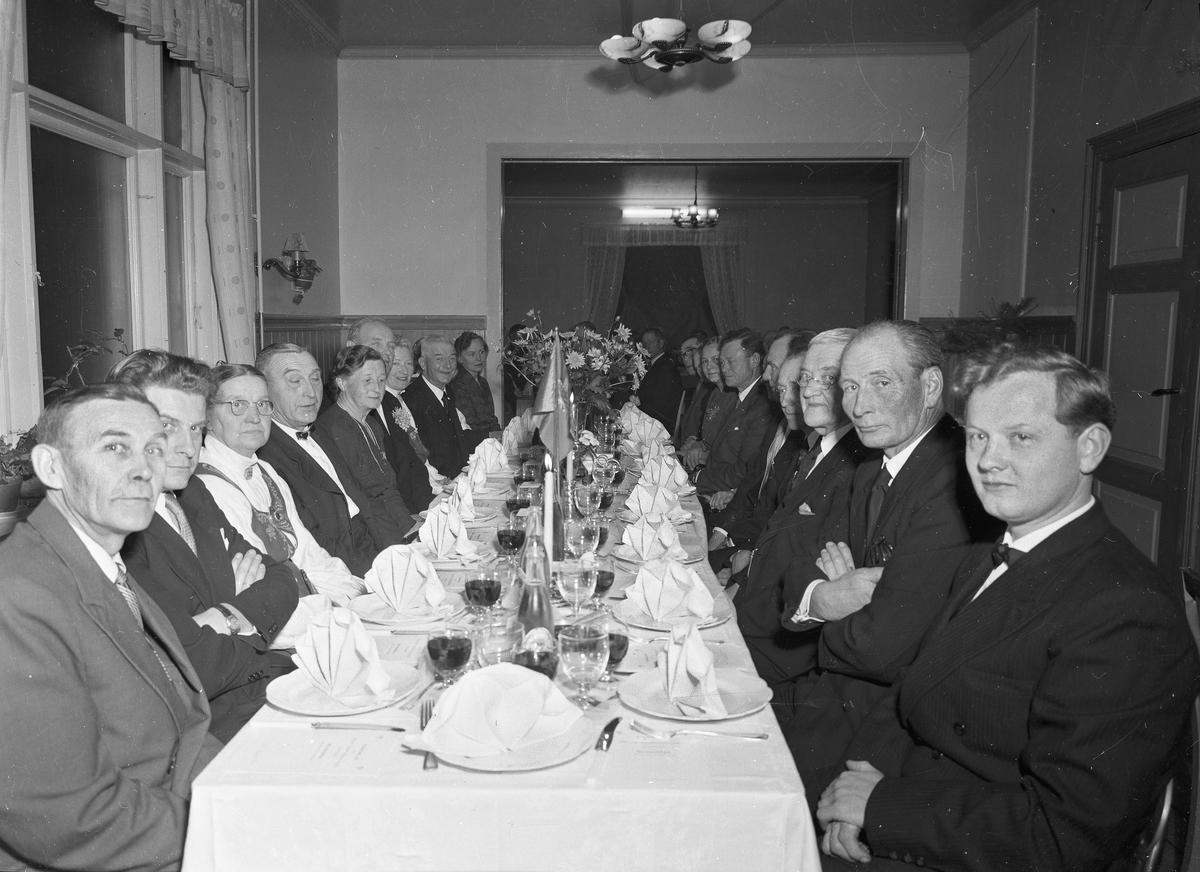 Middagsselskap. Fra v.: Karl Kapaasen, Kjell Amundsen, X, Helge Aas, X, Jens Røkholt. Fra høyre på raden til høyre: X, X, X, Olaf Dønnum, Edvard Fleischer, Hans A Venger, Ingrid Venger.