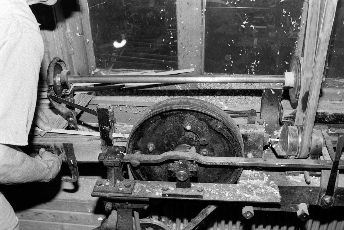 Svartdahl Bruk Bærepinneproduksjon. Demonstrasjon av maskiner. Mating av pinnemaskinen. Emnet føres inn i et spor for dreiing. Operatørens håndbevegelse slutter omtrent på høyde med der fremtrekkshjulet begynner. Til høyre for fremtrekket, med egen remdrift er dreiehjulet. Pinnen mates fram, og dreies rund. Når pinnen er passe lang, stopper matingen, mens det skjæres spor, og pinnen kappes. Per Iversen demonstrerer.