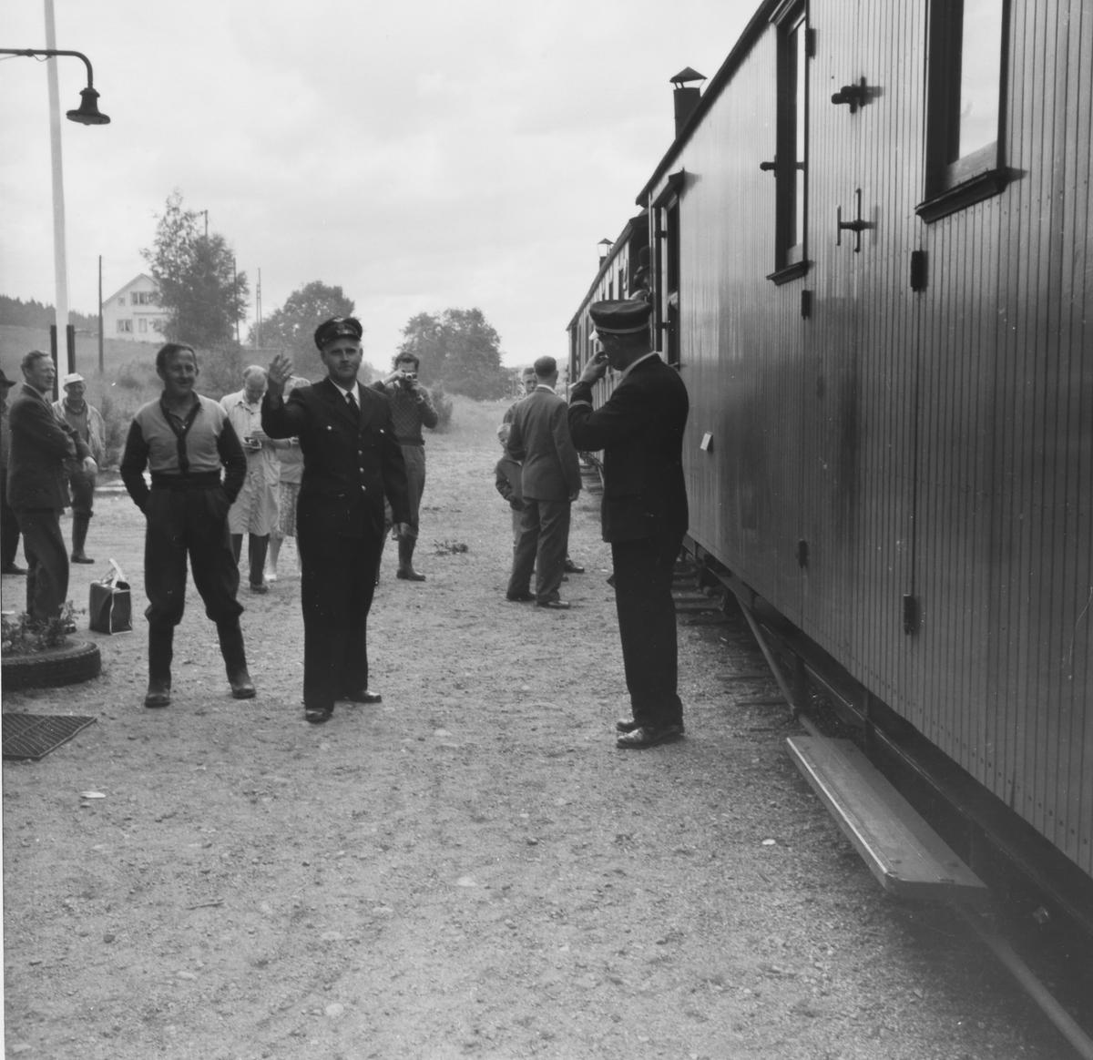 Ekspeditør Kristian Slorbak på Skulerud stasjon gir avgangsmelding for siste ordinære tog til Sørumsand til overkonduktør Håkon Kjelsrud.
