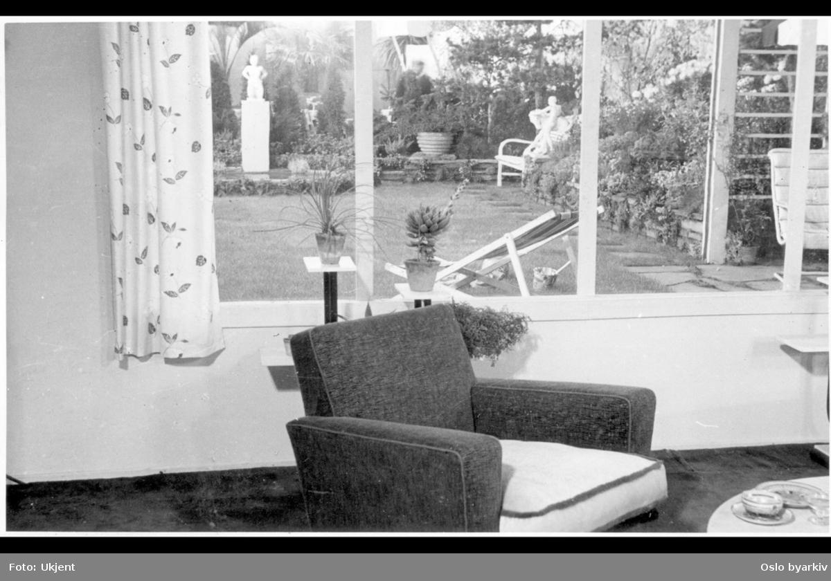 """Utstilling i Roald Amundsens gate, """"Blomstene i hjemmet"""". Innsyn fra husets dagligstue mot blomsterutstillingens have. Plen, havemøbler, (fluktstol), basseng med skulptur, blomsterbed, trær og prydvekster. Albumtittel: """"Utstillinger""""."""