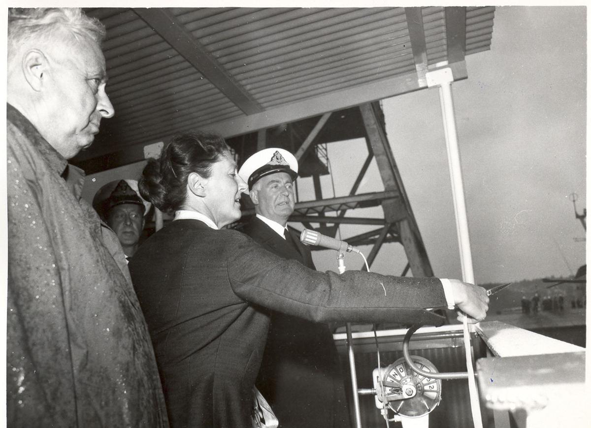 """Sjøsetting og dåp av Oslo-kl.fregatt KNM """"Bergen"""", 1965. Gudmor fru forsvarsminister I. Harlem klipper snoren ved seremonien."""
