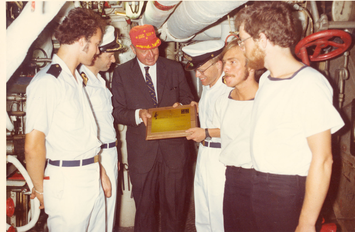 """Oslo-kl.- fregatt KNM """"Trondheim"""" får besøk av Secretary of the Navy J. W. Middeldorf i New York, sommeren 1976. Overrekkelse i 45 gr. varme i kjelerommet. Fra v.: konst (Ma) Torgeir Toverud, dørkformann, Komkapt. K. Granmar/skipssjef, Mr. Middendorf, Kaptlt. (M) I. Poppe/maskinmester, Maskinistassistent R. Andersen/fyrbøter, UM (M) Augun K. Sæverøy."""