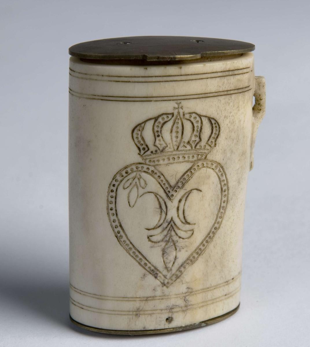 Oval sylindrisk beholder med lokk og bunn av metall. lokket er hengslet til baksiden. Huset har en liten hank for oppheng i bånd/tråd. Gravert monogran med kronet hjerte, reinsdyr.