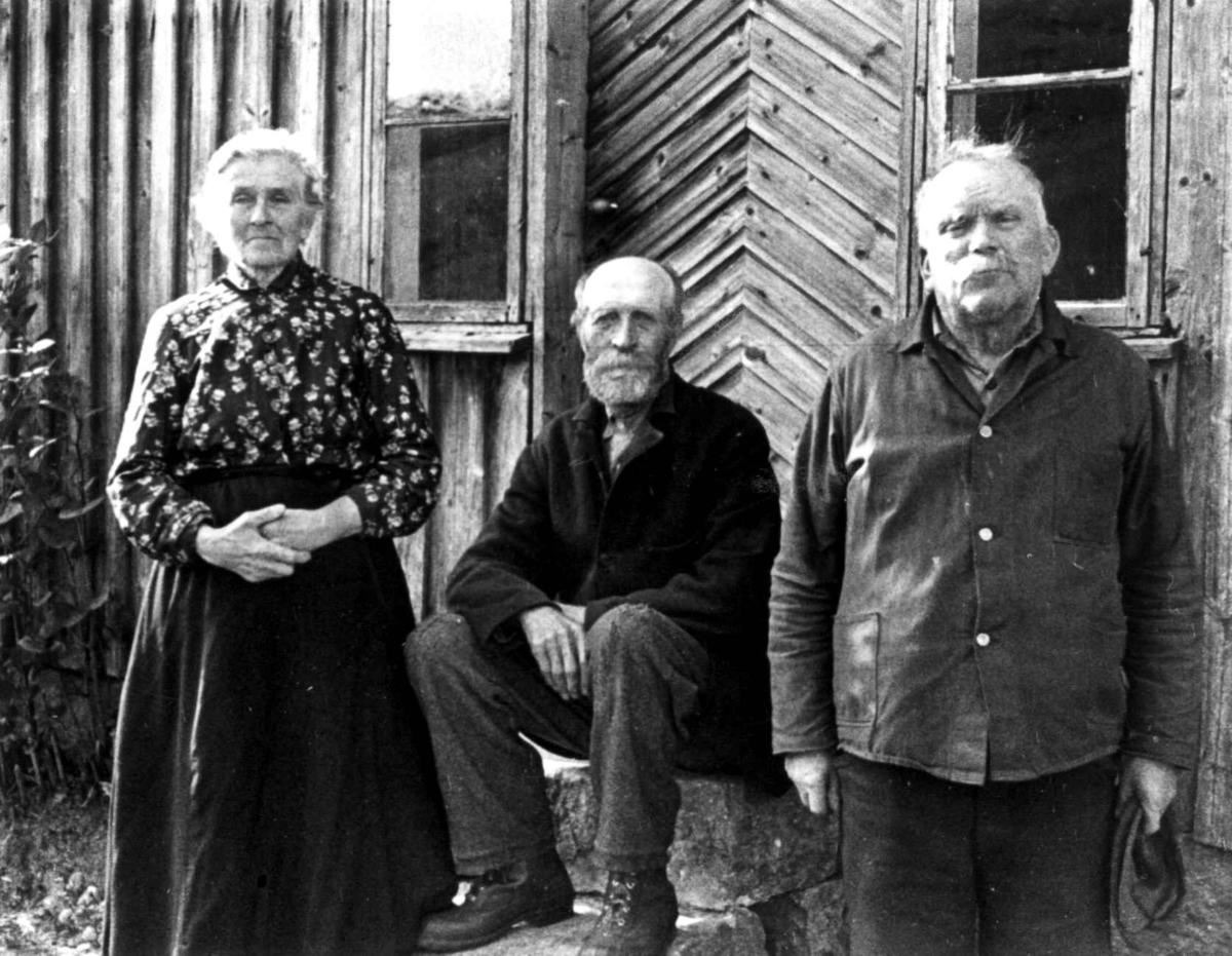 Portrett av Ola H. og Gunvor Røynebo og Per Tobias Kvinlog foran inngangspartiet til et hus. Fjotland, Kvinesdal, 1941.