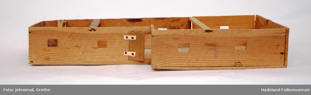 Hjemmelaget trebygninger i 4 deler. a)Kasse innredet som fjøs: lengde 38,5 cm, br. 24,5 cm, høyde tot. 24,5 cm. b) Kasse med vinduer og dører. L.47,5 cm. Br. 20/14 cm. H 8 cm. c) Loft. Gavler med ukomplett gulv og takåser. L. 54 cm. Br. 35 cm. H 10,5 cm. d) Borg
