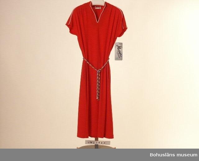 """Röd klänning med med holkärm i tunn jerseykvalitet. Vita passpoalkantningar runt halsöppning och axelparti. Hel framdel med V-ringad halsringning med smal ståkrage. Infälltt axelparti med två veck fram och ett veck bak. Tvåvådig bakdel. Infällda fickor i samma material i sidsömmarna. Hällor i sidorna med skärp av bomullssnodd med avslutande knut med kardeler i vitt, rött, ljusblått, mörkblått, gult, grönt, brunt och violett. Ofodrad. Etikett i halslinningen med med texten: """"Magna SVENSK KONFEKTION 38"""" och på baksidan skötselråd med bland annat tvättsymbol 40 grader.  I ärmen vidhängande papperetikett i plastsnöre med texten: """"Magna Classic SVENSKTILLVERKAD På andra sidan med texten: Magna 451 02 UDDEVALLA SVENSKTILLVERKAD Model  M125 Colour  3 Quality  328 Size  38 Com,position pol 67% bom. 33% Price 345:- Vid platsen för pris har Prylmarknaden fäst en klisterlapp med texten """"Kr 45.-"""" Obegagnad vid förvärvet. Sommarkläningen är designad av Birgitta Frost-Nyström, designer på Magna mellan åren 1970 - 1988. Detta var en populär modell som tillverkades i flera olika kulörta färger (de som snodden innehåller). Samma snodd användes till alla färgställningarna. En nackdel med tyget var att det lätt fick noppor.  För ytterligare uppgifter om förvärvet och övrigt material rörande Magnas produktion i museets samlingar, bl.a. dokumentation 1998, se UM027416."""