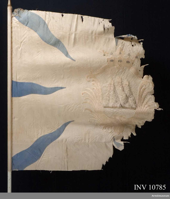 Grupp B.   Duk av vitt fyrskaftat fansiden (kypert) med från hörn o sidornas mitt, inåtgående, 8 st flammor av blå taft. Sydd av tre våder en bredare i mitten, smalare upptill och nedtill. I mitten broderat Västmanlands sköldemärke, tre eldsprutande berg (milor) med gula flammor omgivna av en sköld bildad av  stiliserande palmkvistar och krönt av en öppen krona. Skölden och kronan i plattsöm av gult silke, den senare med pärlor i silver och stenar i rött och blått silke. Bergen i schattersöm i grå och bruna silken flammor av gula silken. Kantad med sidenband. Stången av furu, vitmålad. Doppsko av mässing. Spets  av förgylld mässing. Bladet med Karl XIV (Johans) krönta spegelmonogram inom ram av lager. Krönt av en strålande sol. Fodralet är i bomullstyg längd 1480 mm.