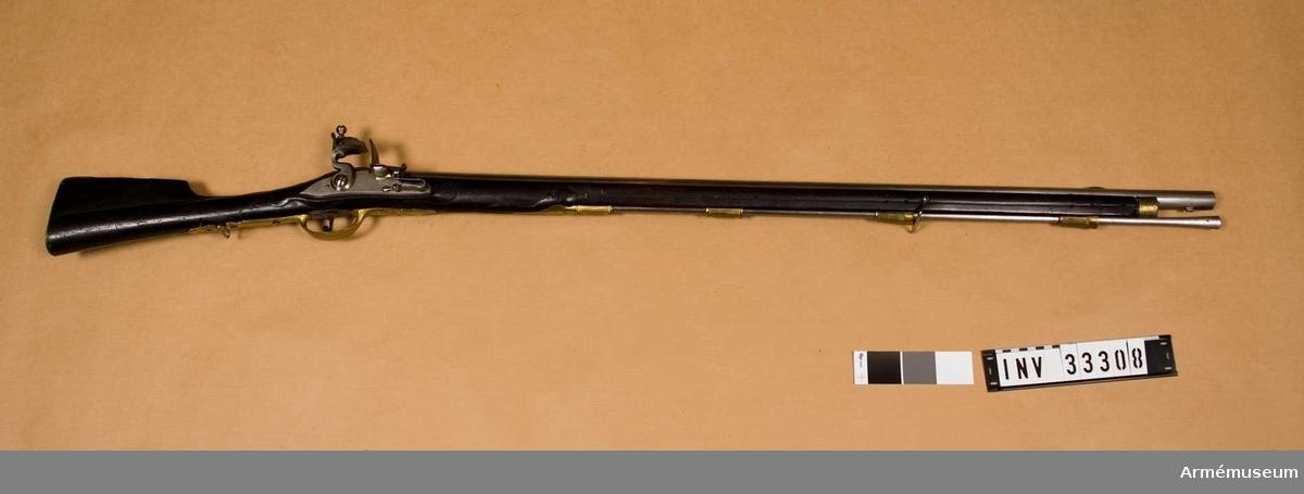 """Grupp E II. Med flintlås avsett för bajonett m/1773, svartbetsad och på kolven mässingsplåt med Carl af Wiirtenbergs namnchiffer (ej Preussiskt). Vid geväret är fästad en äldre etikett: """"I.) nr 324. Gevär med flintlås, afsedt för bajonett m/1773, med å kolvplåten namnchiffer CG (spegelvänt), Carl av Würtenberg, hvilken under Fredrik IIs regering var chef för preussiska infanteriregemente N:r 46. Preussen."""""""