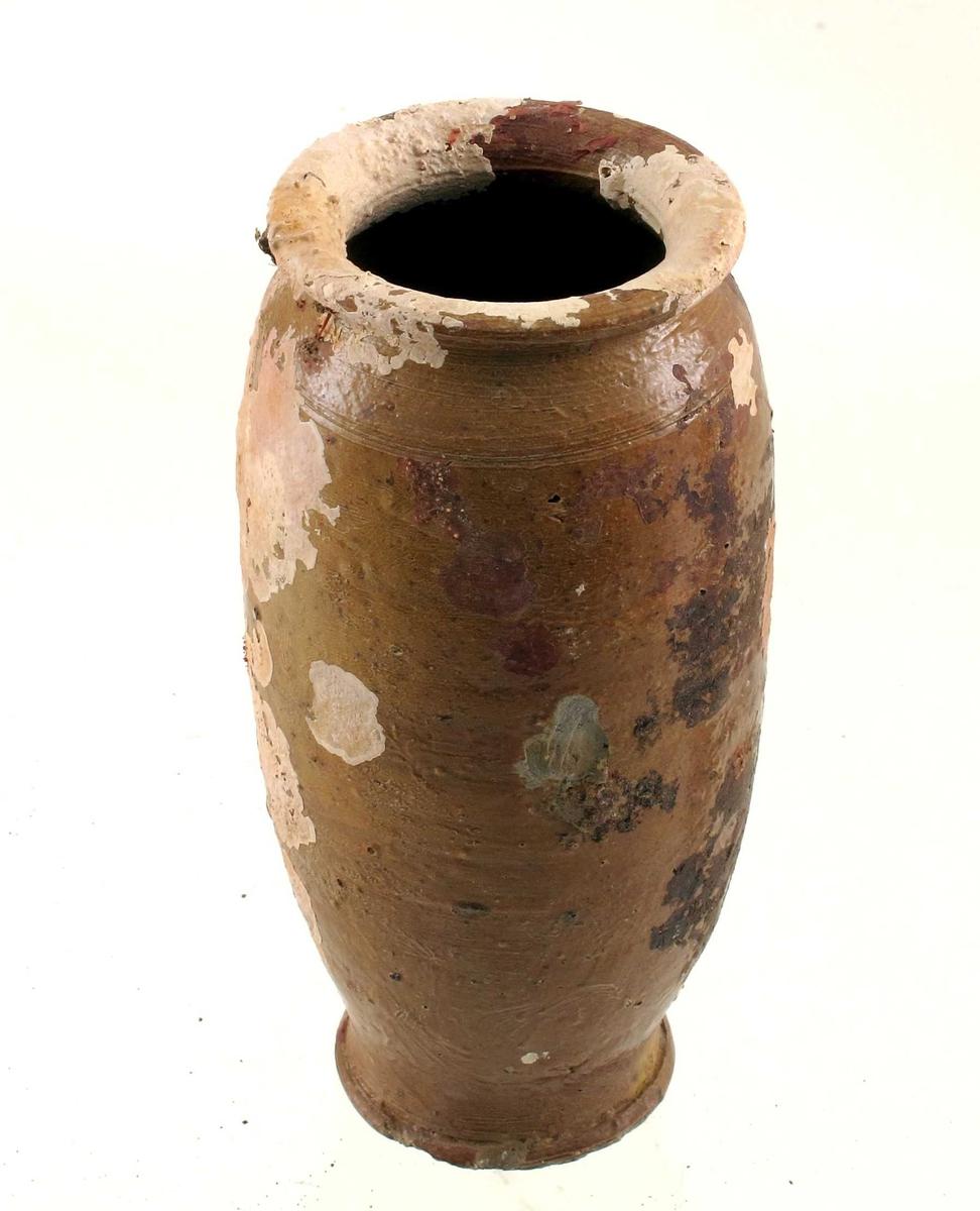 Leirtøy, grått gods, brun glasur  Liten krukke av samme type og muligens samme fabrikat som foregående  Smal, med en ring i overgangen til halsen. Smal brem.