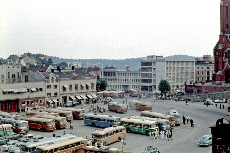 Arendal senturm. Utsikt fra Strømsbuveien, Rutebilstasjonen m ADS-busser. Posthuset, Trefoldighetskirken m.m. På dette tidspunkt er både gammel rutebilstasjon på Tyholmen og ny på Sanden i bruk