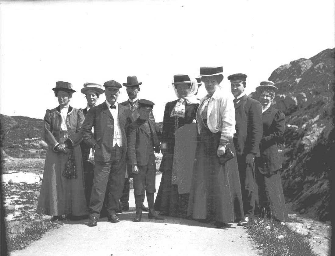 Friluftsliv - gruppebilde - draktskikk. En gruppe mennesker på utflukt. Kvinnene kledd i side kjoler med hatt. Den ene av kvinnene bærer et pledd.