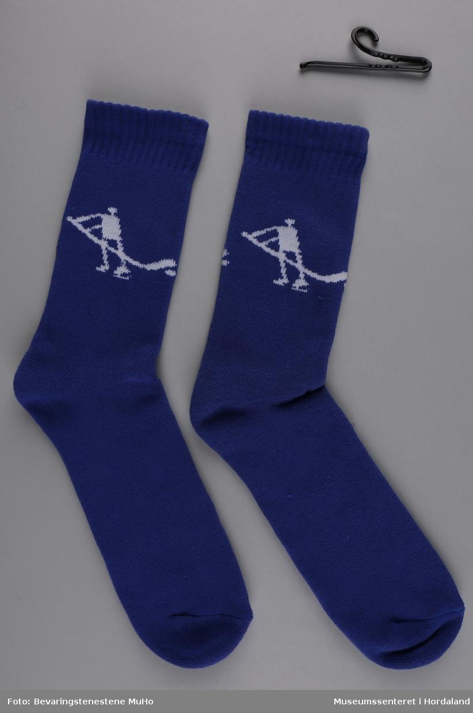 Eitt par blå frottésokkar med kvitt mønster. Mønsteret forestiller ein stilisert mannsfigur (inspirert av hellerisningar) som spelar ishockey.  Sokkane vart produserte til Vinter-OL på Lillehammer i 1994.