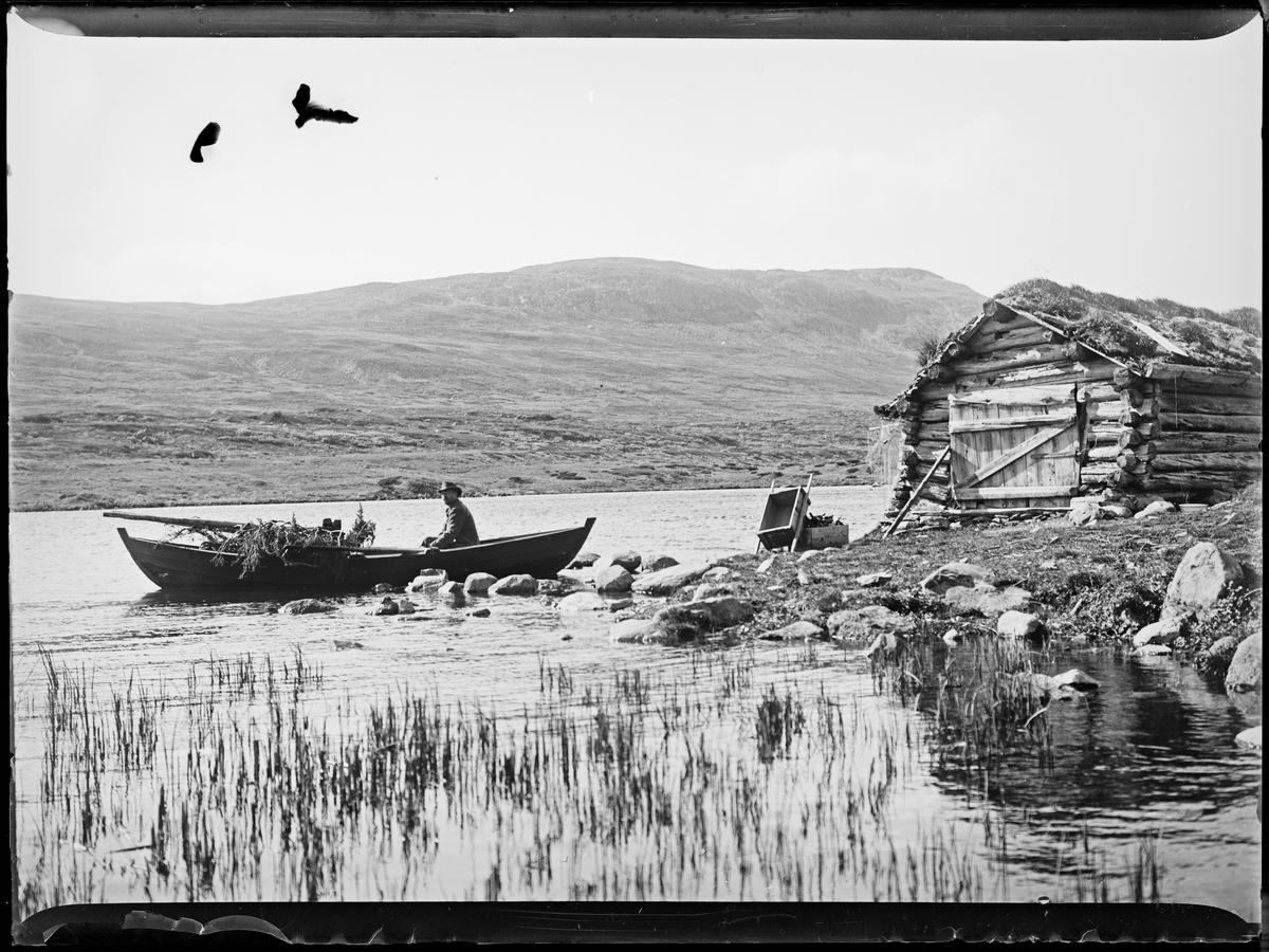 """Heimdalen 1906"" (inskr eske). Fjellandskap. Sjølisætra ved Atnsjøen i Rondane. En mann sitter i en robåt. Et laftet båthus ligger rett ved vannet."