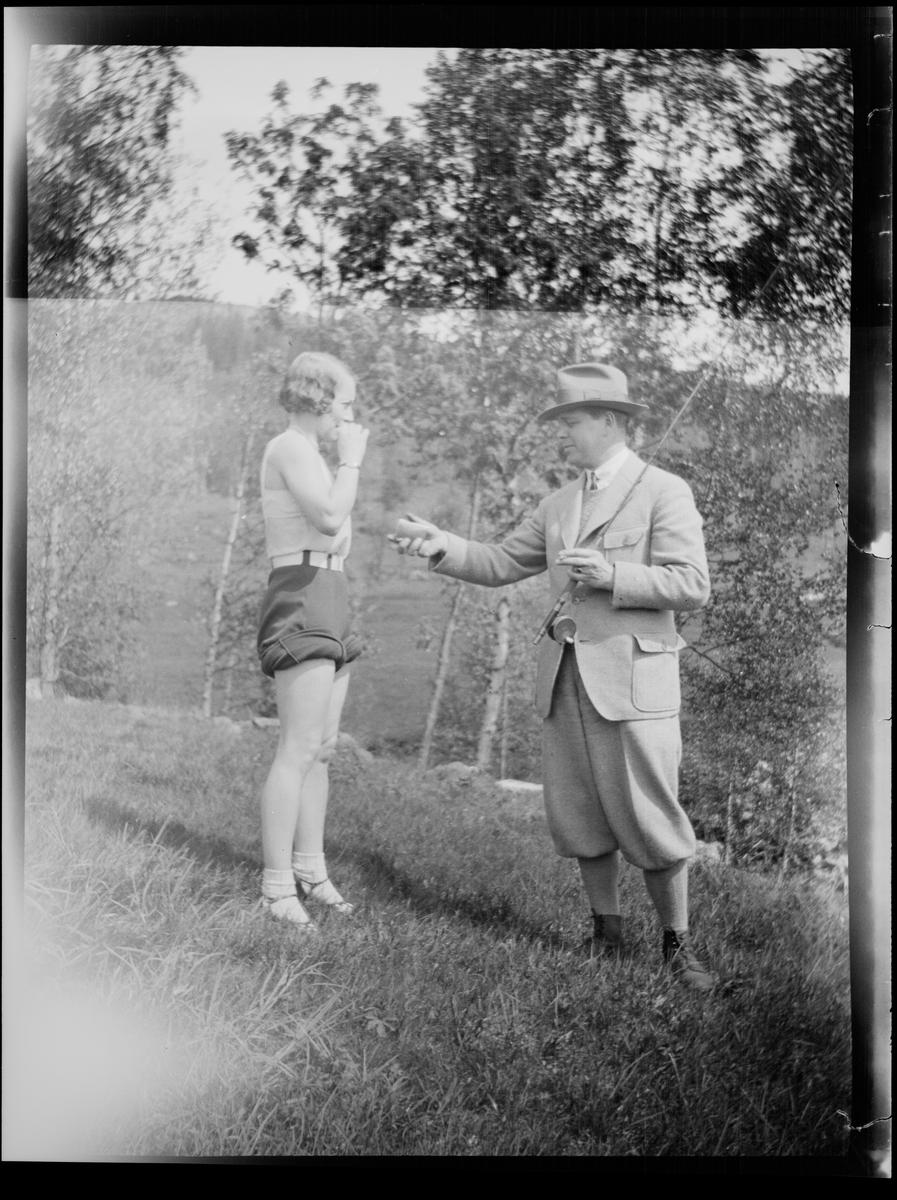 En mann kledt i fritidstøy bærer en fiskestang samtidig som han strekker fram hånden og byr en dame, også kledt for fritid, på sigaretter. De står på en røff gressplen kantet med løvtrær.