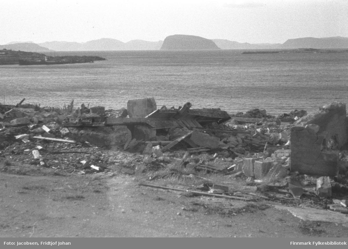 Ruiner av Hauans materialhandel. Foran på bildet er Nedre Grønnevoldsgate. Oppe til venstre på bildet ses Hammerfest-neset. En ganske stor fraktebåt ligger fortøyd rett foran neset. Øya Håja med Sørøya noe diffust ses øverst på bildet. Fuglenesodden ses oppe til høyre.