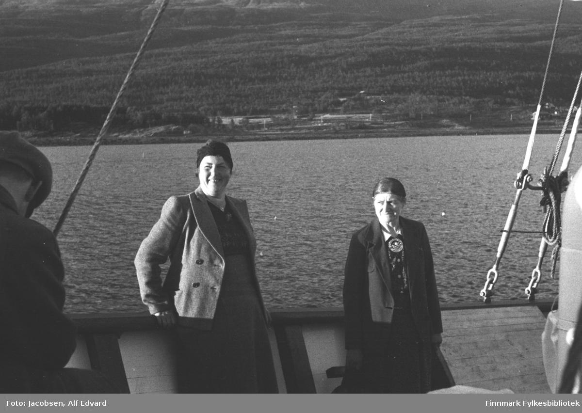 To kvinner og en mann fotografert ombord på en båt. Helt til venstre på bildet ses en liten del av en mann. Han har ganske mørk jakke og en skyggelue på hodet. I midten står Borgny Baug Pettersen fra Lakselv. Hun lener seg litt mot rekka på båten og er iført en ganske lys kåpe og en mørkere kjole. Hun har en mørk lue eller tørkle på hodet og i halsen ses et smykke. Den ukjente damen til høyre på bildet har mørk kåpe og skjørt. Hun har en hvit bluse-krage og en stor, blank sølje i halsen. Siden på båten er lys med svart håndlist og stolper. Flere tau er festet til rekka og går sannsynligvis opp til masta. I bakgrunnen ses et stor landområde som skrår svakt oppover. Området er stort sett skogkledt. El-stolper står langs strandkanten, sansynligvis langs en vei. Helt til høyre på bildet står noen hus nederst i terrenget.
