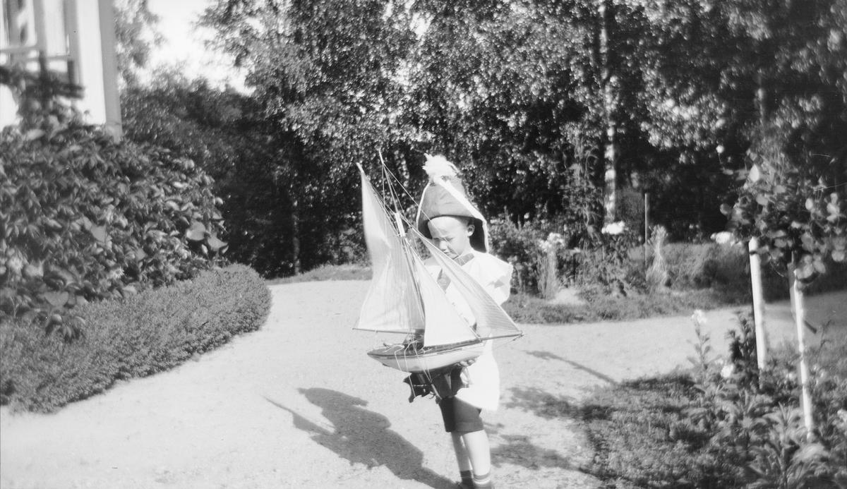 """Iacob Ihlen Mathiesen har kledd seg ut som kaptein, har """"kapteinshatt"""" på hodet og holder en liten seilbåt. Han står på gruslagte hagestier, kranset med frodige blomsterbed, utenfor hovedhuset."""