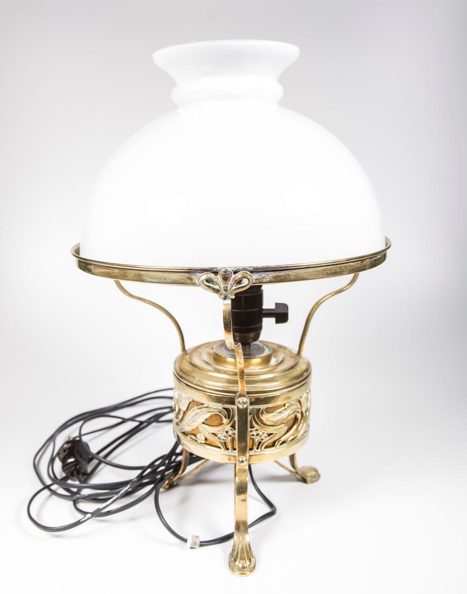 Skrivebordslampe i jugend-stil. Halvkuleformet glasskjerm. Tre ben og tre holdere til skjermen. Deekorelementer på ben og kropp.