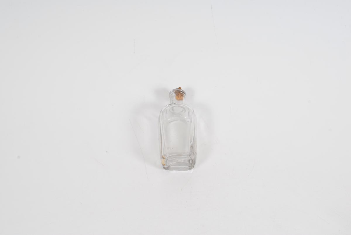 Gglasset er bueformet ved flaskens hjørner/kanter og i bunnen er det et enkelt blomsterlignende motiv.