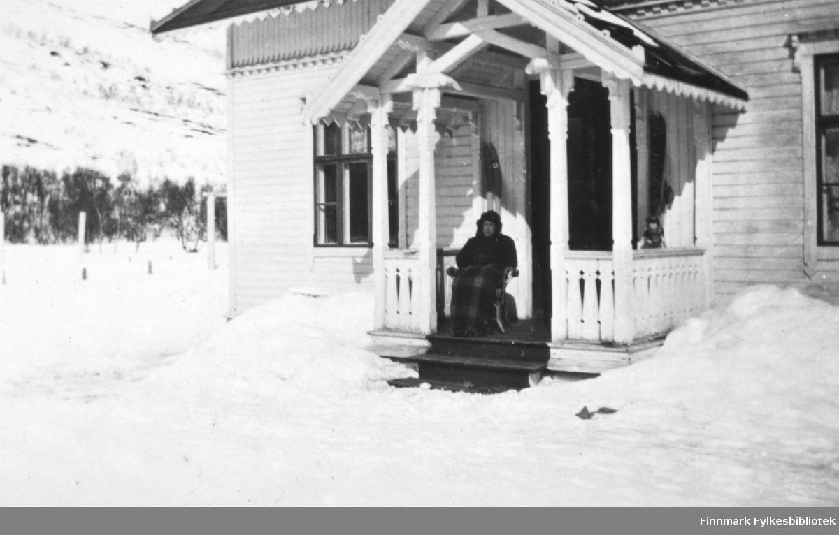 Aprilidyl 1917. En mann sitter i en kurvstol, på trappen til inngangspartiet til Fredenlund. Det er sol og mannen har et rutete ullteppe liggende over beina. Han har på seg lue. Mot veggen lener det seg et par ski både til høyre og til venstre for døren. Det er snø på bakken og vårsteming.