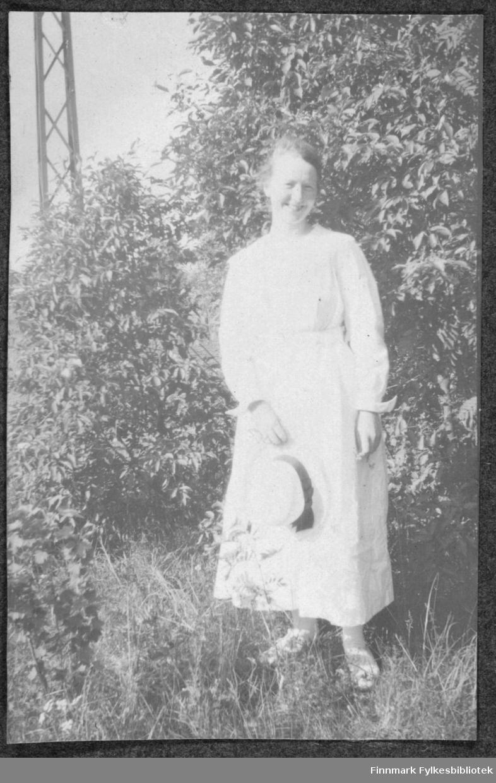Portrett av kvinne i hvit kjole med hatt i hånden. Sommer.