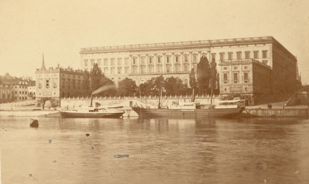 Två fartyg vid Logårdskajen vid Stockholms slott. Det vänstra är ångfartyget Fredriksborg, byggt 1869 på W Lindbergs varv i Stockholm. Hon såldes 1882 till Höganäs och fick då namnet Höganäs. Fartyget till höger hette Norrland och byggdes 1853 i Aberdeen av svenska ägare som Daniel. Hon förliste 1866, bärgades två år senare, reparerades och fick 1870 namnet Norrland. Bilden är således tagen mellan 1870 och 1881. Norrland namnades 1886 om till Hudiksvall II och övergick 1888 i norsk ägo under namnet Trafik.