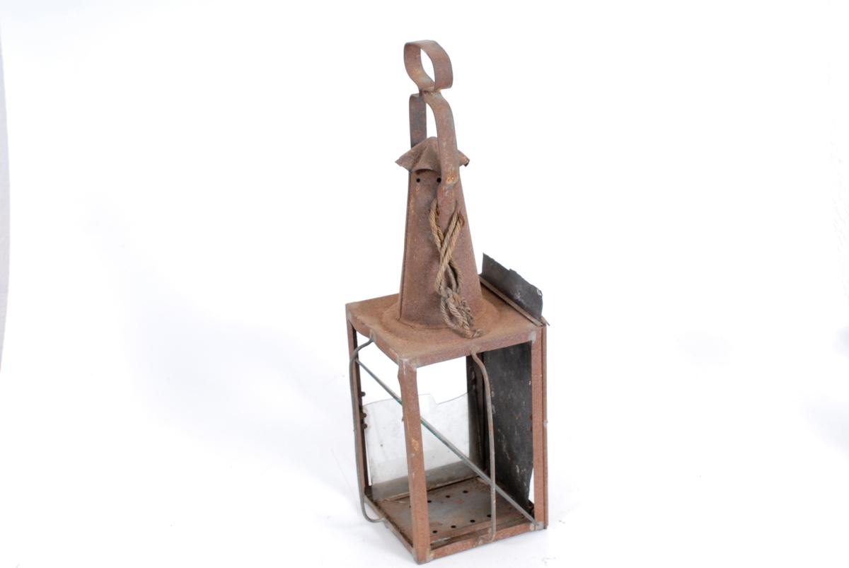 """Form: Firkantet. Sidestykkene av glass festet med *23 ..små stifter. Bunnstykket er loddet på og har små trekk- hull. Lykta smalner av oppover mot en """"skorstein"""" med bølget tak. Foran glass-sidestykkene er loddet på gitter for beskyttelse. Hank m/svungen form, er festet til """"skor- steinen"""". Gave fra Nils Ladderud."""