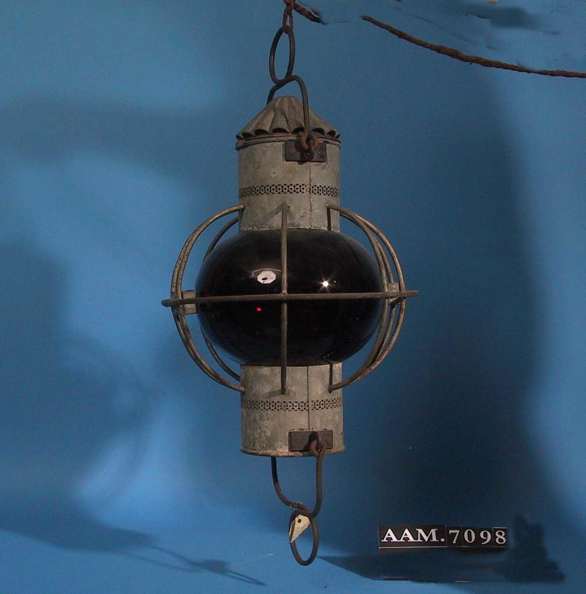Ankerlanterne.  Jernstenger, blikk, dyprødt   glass. To blikksylindre med dyprød glasskuppel imellom, beskyttet av  jernstenger. Brenneren tennes fra undersiden. Hank i begge ender.