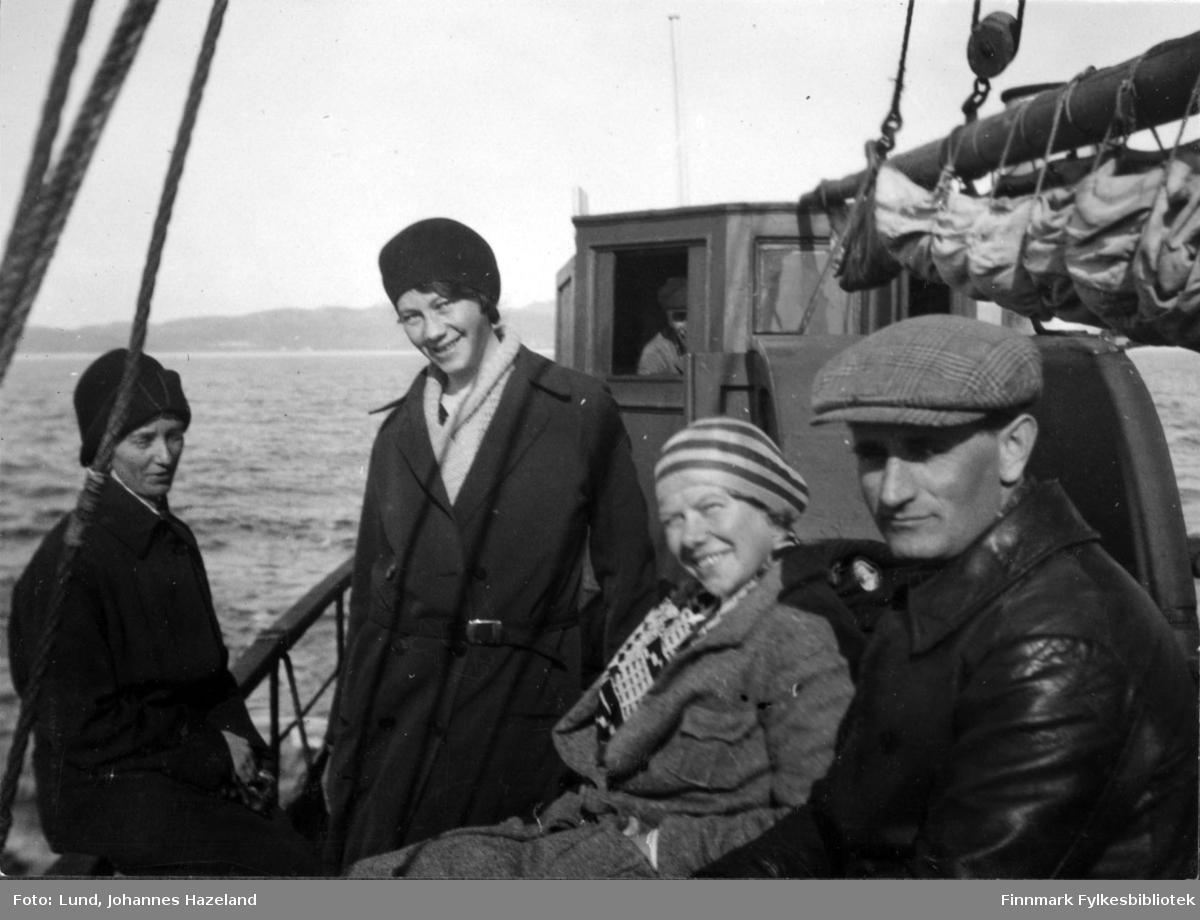 Tre kvinner og en mann fotografert på dekket av en båt