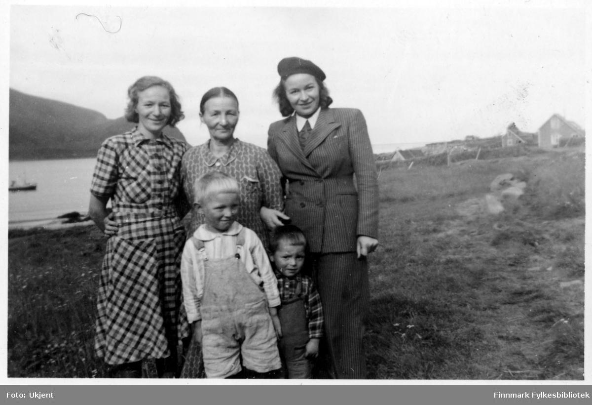 Et Kvivesen familieportrett. Her står Ellen Kvivesen i midten omringet av sine barn og barnebarn. Til venstre for Ellen står hennes datter, Gerda Jensen. Til høyre, hennes datter Alis Kvive Andersen. De to guttene i første rekke er Gerdas sønner: Arne og Gunvald Jensen. Alle er fra Nuvsvåg. Gerda og Ellen er kledd i kjoler. Alis er kledd i en stripete dress og en lue. Guttene har på seg olabukser og skjorter. I bakgrunnen kan man se havet, fjell og enkelte bygninger.