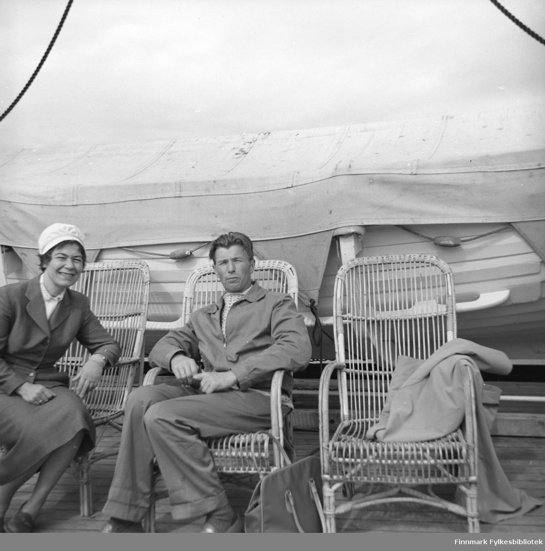 Jenny og Eino fotografert sittende i dekkstoler rett foran en livbåt.